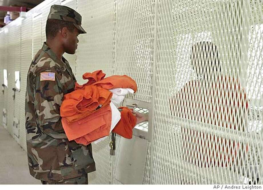 ** FILE ** A U.S. Military Police officer gives clean clothes and linen to a detainee before prayer in Camp Delta at the Guantanamo Bay Naval Base, Cuba in this June 30, 2004 file photo. The government is holding about 550 terrorist suspects at the U.S. Navy base in Cuba. An additional 214 have been released since the facility opened in January 2002 _ some into the custody of their home governments, others freed outright. (AP Photo/Andres Leighton) PHOTO REVIEWED BY US MILITARY A JUNE 30, 2004 FILE PHOTO Photo: ANDRES LEIGHTON