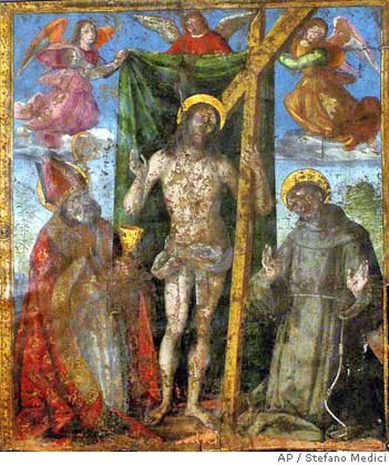 A two-meter (6.5 feet) tall linen religious banner showing a risen Christ between a kneeling St. Ubaldo and St. Francis of Assisi, believed to be painted by Renaissance master Raphael in 1498-99, is seen on exhibition during it's unveiling in the Umbrian city of Gubbio, central Italy, Wednesday, Oct. 20, 2004. The letters R and V, standing for Raphael Urbinas, the artist's Latin name, were found on the banner, once used for in religious processions, after a three-year restoration. (AP Photo/Stefano Medici) Datebook#Datebook#Chronicle#10/25/2004#ALL#5star##0422423544 Photo: STEFANO MEDICI