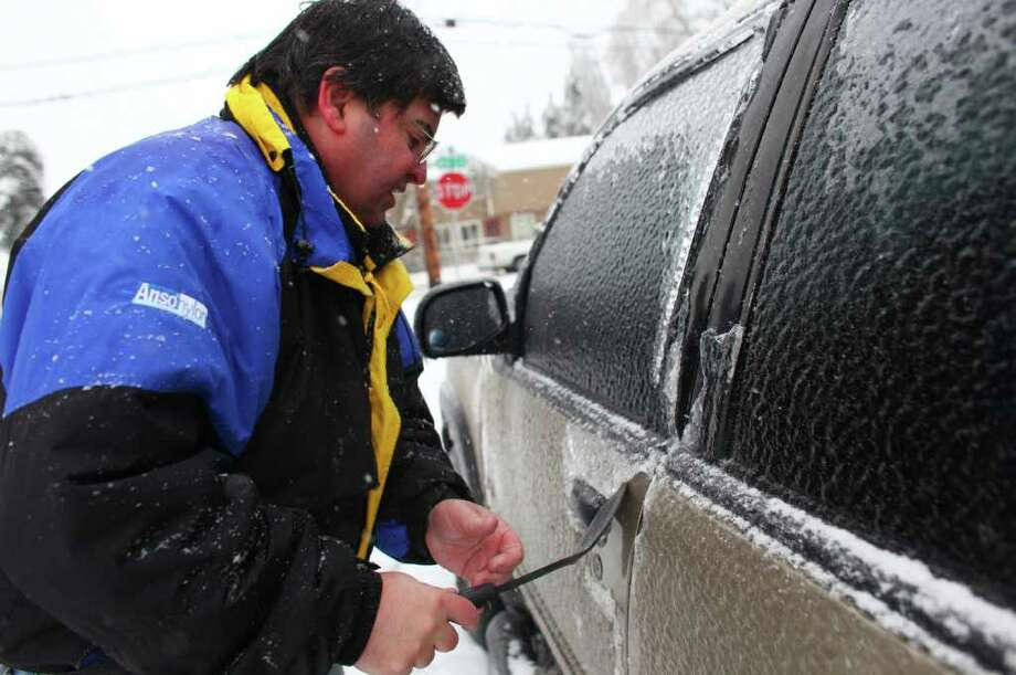 Harvey Berry works to chisel a car door open with a spatula on Thursday, January 19, 2012 in Auburn. An ice storm brought tree branches and power lines down across the region. Photo: JOSHUA TRUJILLO / SEATTLEPI.COM