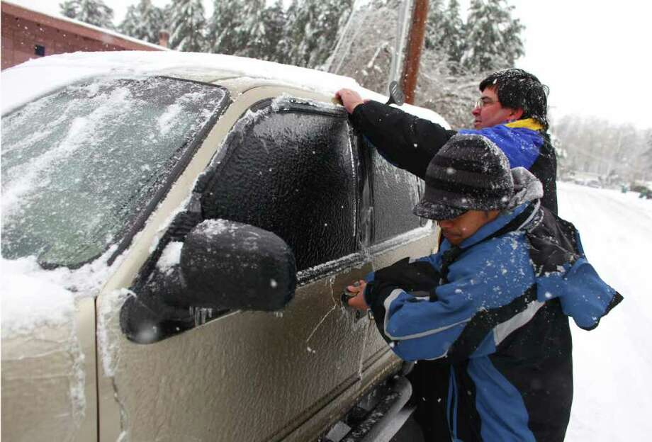 Alan Laborce and Harvey Berry work to chisel open a car door on Thursday, January 19, 2012 in Auburn. An ice storm brought tree branches and power lines down across the region. Photo: JOSHUA TRUJILLO / SEATTLEPI.COM