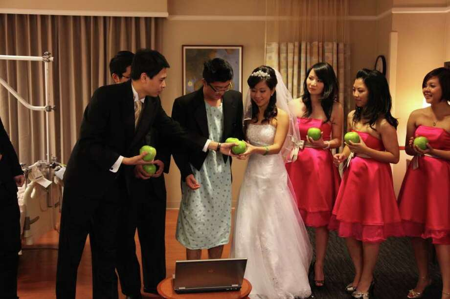 Holding apples, a symbol of peace and health, David Wang and Sharon Li recite their wedding vows in a hospital room after the groom's emergency appendectomy drastically changed their plans. Attendants include, from left, Jian Wang,  JP Li, Irene Shi and Rachel Li. Photo: Family Photo / IMG_5206.JPG