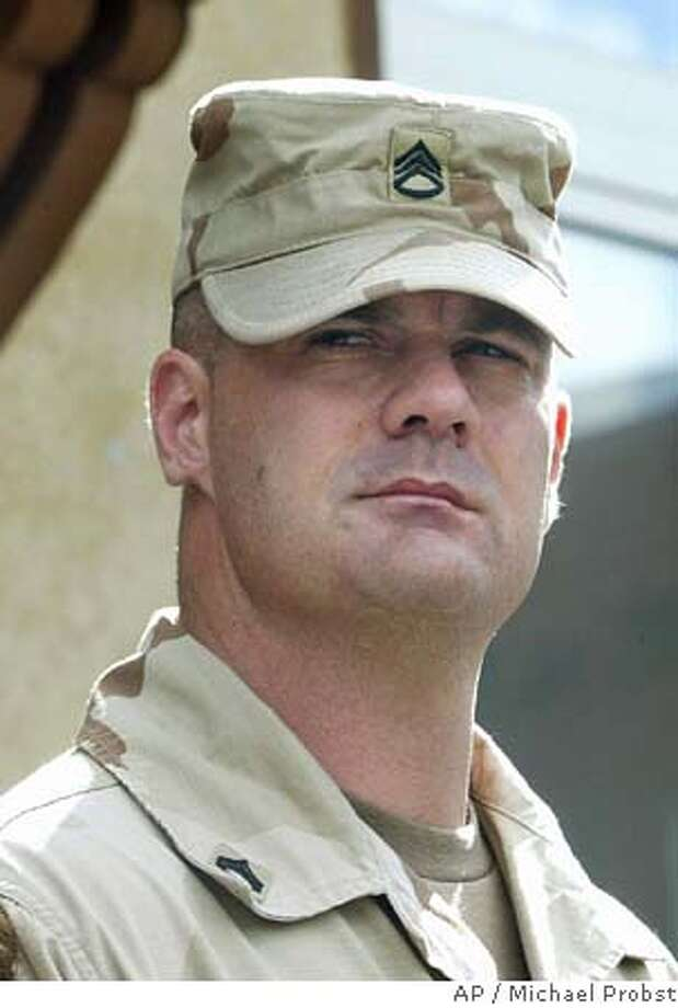 ** FILE ** U.S. Army Staff Sgt. Ivan L.Frederick meets the media in front of the U.S. military court at Taylor Barracks in Mannheim, southern Germany, following his hearing, in this Aug. 24, 2004 file photo. Frederick, the highest-ranking soldier charged in the Abu Ghraib scandal, pleaded guilty Wednesday Oct. 20, 2004 to five charges of abusing Iraqi detainees at the prison as a two-day court-martial opened at a U.S. base in Baghdad. (AP Photo/Michael Probst, File) AUG. 24, 2004 FILE PHOTO Nation#MainNews#Chronicle#10/21/2004#ALL#5star##0422422739 Photo: MICHAEL PROBST