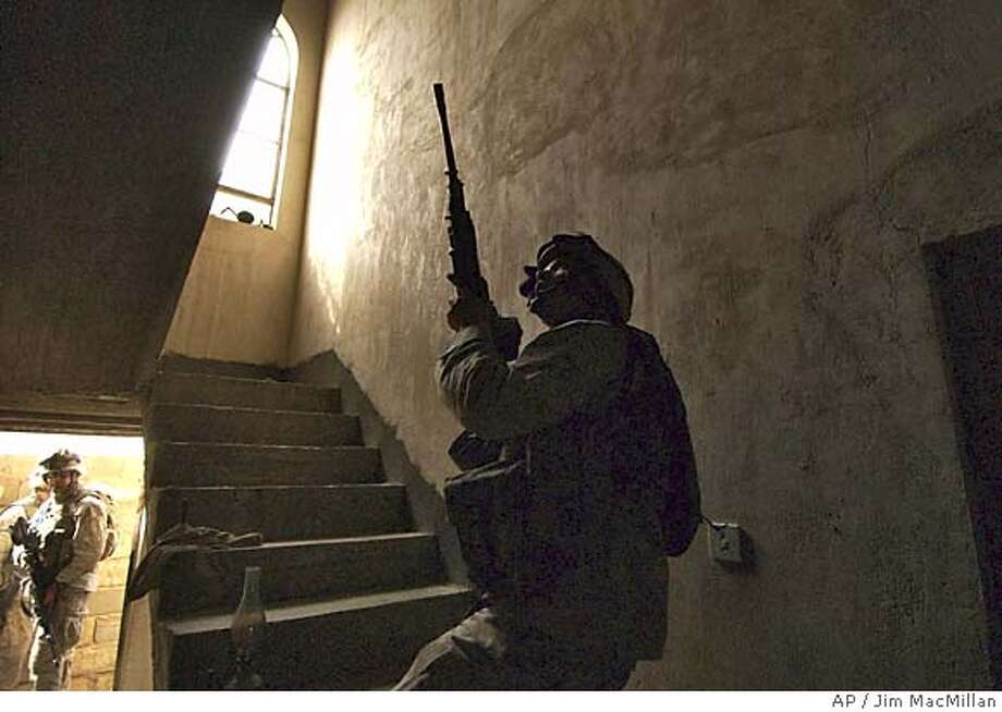 U.S. Marines from the 2nd Battalion, 5th Marine Regiment search a building in Ramadi, Iraq, Monday Oct. 25, 2004. Rebels and U.S. forces battled in Ramadi earlier Monday, and hospital officials reported three Iraqis were killed during the fighting. Insurgents bombed one American security patrol and ambushed a separate convoy with small arms, rocket-propelled grenades and an improvised explosive, the U.S. military said. No Americans were injured. (AP Photo/Jim MacMillan) Ran on: 10-26-2004  U.S. Marines search a building in Ramadi, where rebel and U.S. forces battled. Hospital officials reported three Iraqis were killed. Photo: JIM MACMILLAN
