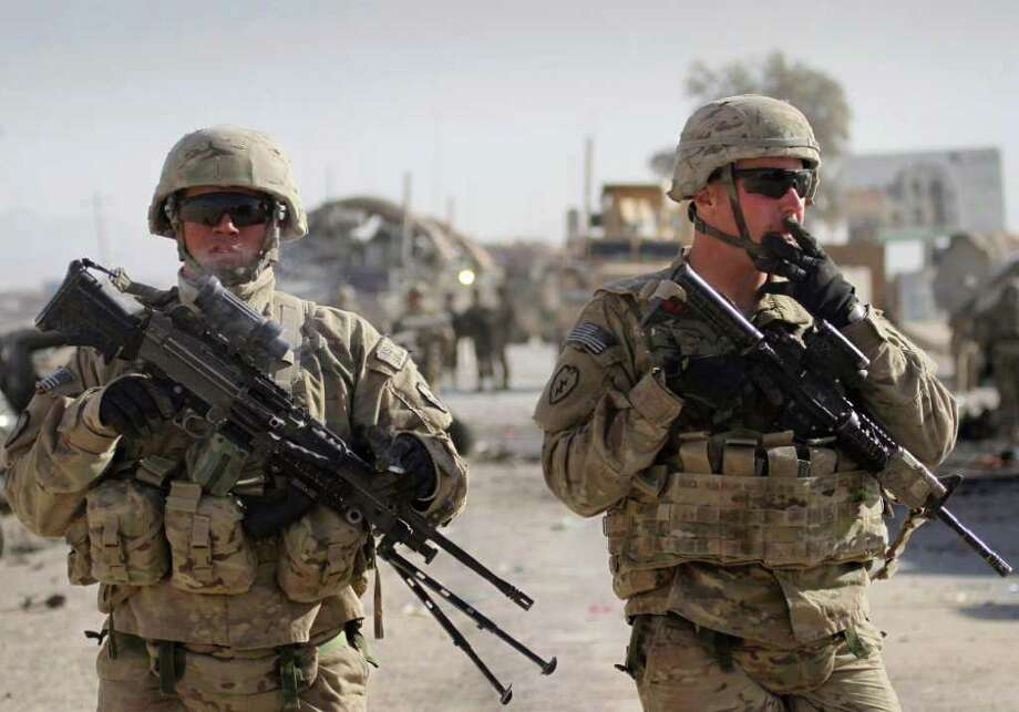 U.S. soldiers with the NATO led International Security Assistance Force (ISAF) stand guard at the scene of a suicide attack in Kandahar south of Kabul, Afghanistan, Thursday, Jan. 19, 2012. A suicide attacker blew himself up Thursday at an entrance to a sprawling base for U.S. and NATO operations in southern Afghanistan, killing at least six civilians, police said. (AP Photo/Allauddin Khan) Photo: Allauddin Khan / AP