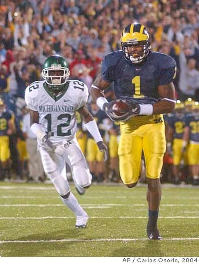 Michigan wide receiver Braylon Edwards (1) outruns Michigan State cornerback Aston Watson (12) for a touchdown during the third overtime period at Michigan Stadium in Ann Arbor, Mich., Saturday, Oct. 30,, 2004. Michigan defeated Michigan State 45-37 in triple overtime. (AP Photo/Carlos Osorio) Ran on: 10-31-2004  Michigan's Braylon Edwards outruns MSU's Ashton Watson for a TD in the third overtime. Ran on: 10-31-2004  Michigan's Braylon Edwards outruns MSU's Ashton Watson for a TD in the third overtime. Ran on: 10-31-2004  Michigan's Braylon Edwards outruns MSU's Ashton Watson for a TD in the third overtime. Ran on: 03-31-2005  Michigan receiver Braylon Edwards is among the candidates to be selected by the 49ers with their No. 1 pick in the NFL Draft. Ran on: 03-31-2005  Michigan receiver Braylon Edwards is among the candidates to be selected by the 49ers with their No. 1 pick in the NFL Draft. Photo: CARLOS OSORIO