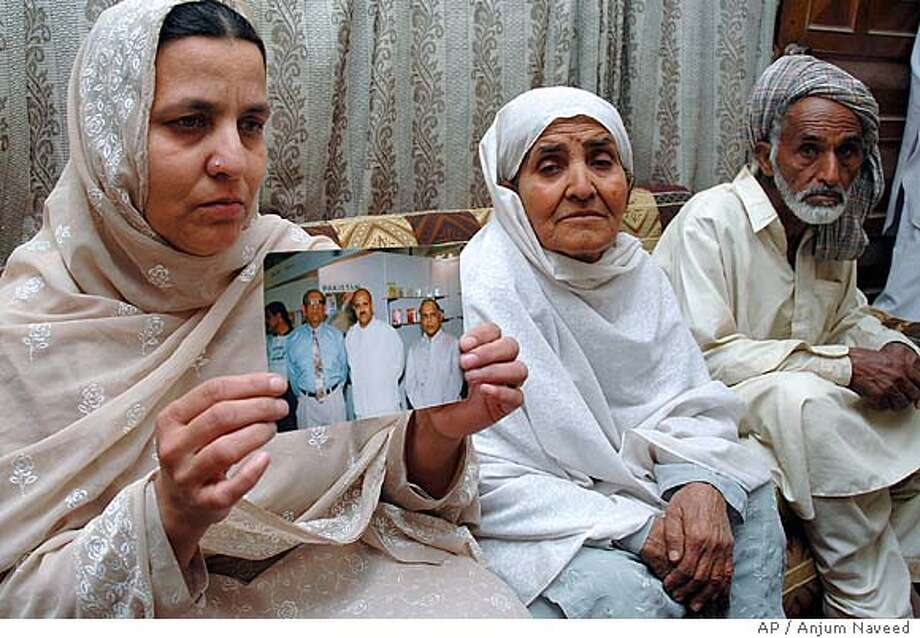 Family members of Malik Mohammad Javed, a Pakistani diplomat kidnapped in Iraq, from left: Javed's wife Abida Bibi, mother Razia Bibi, and father Malik Aslam, show a photo of Javed (pictured at centre) to the media at his home in Islamabad, Pakistan, Sunday, April 10, 2005. Militants in Iraq kidnapped the Pakistani diplomat, the Foreign Ministry said Sunday. (AP Photo/Anjum Naveed) Photo: ANJUM NAVEED