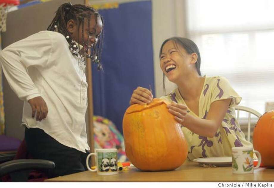 children190138_mk.jpg  Kiki Clay and her mentor Thuy Nguyen laugh as they carve a pumpkin together at the offices of Friends of the Children in San Francisco.  Kiki Clay is on of Thuy Nguyen's mentees brought to her through the Friends of the Children program which is trying connect at-risk kids with possative role models. 10/16/04  MIKE KEPKA/The Chronicle MANADATORY CREDIT FOR PHOTOG AND SF CHRONICLE/ -MAGS OUT Metro#MainNews#Chronicle#10/19/2004#ALL#5star##0422417049 Photo: MIKE KEPKA
