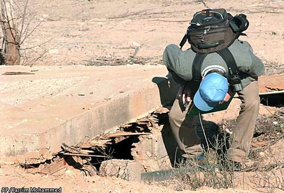 A member of the U.N. weapons inspectors team peers into a tiny shelter before entering to inspect more closely at the al-Amer factory in Ramadi province, Iraq, some 90 kilometers (56 miles) northwest of Baghdad Monday, Jan. 13, 2003. (AP Photo/Jassim Mohammed) Photo: JASSIM MOHAMMED