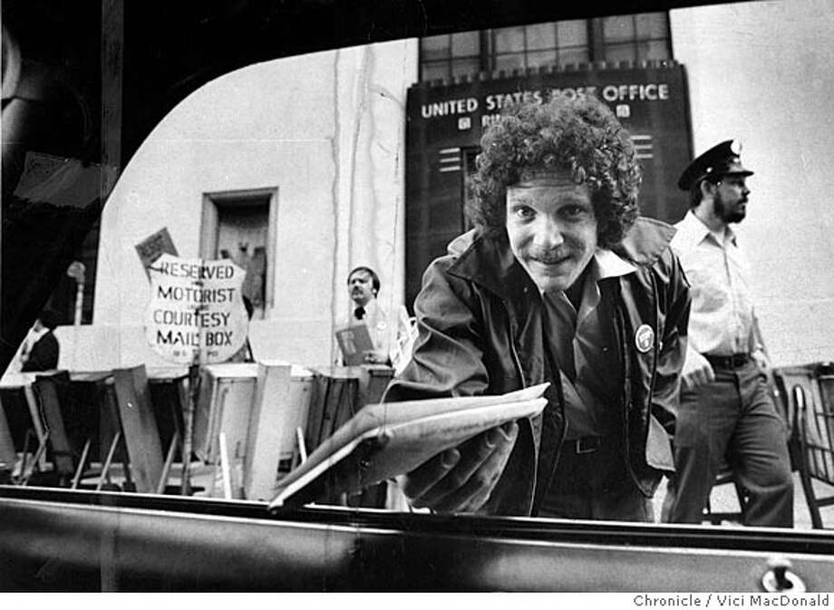 Neil Zarchin, who calls himself a combination postal clerk and traffic cop. reaches into a car at Rincon Annex to take a tax retrun on Apirl 15, 1980.  Chronicle Photo Vici MacDonald