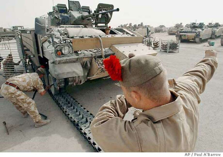 Members of the First Battalion Black Watch check a military vehicle at Battalion Headquarters at Shaibah Logistics Base in Al Basra Province, southern Iraq on Monday Oct. 18, 2004. Britain's Defence Secretary Geoff Hoon announced in the House of Commons in London Thursday Oct. 21, 2004, that Britain has agreed Thursday to send 850 British soldiers closer to Baghdad, freeing U.S. troops to step up attacks on insurgent strongholds in Iraq. Hoon said an armored battlegroup from the First Battalion Black Watch would move from its base in southern Iraq to a volatile area west of Baghdad, where Sunni insurgents have been carrying out daily attacks on U.S. troops and Iraqis. (AP Photo/Paul A'Barrow, Royal Navy, Crown Copyright) ** ** Ran on: 10-22-2004  Members of Britain's Black Watch Regiment, which will provide soldiers, work on a vehicle in Basra. Photo: PAUL A' BARROW