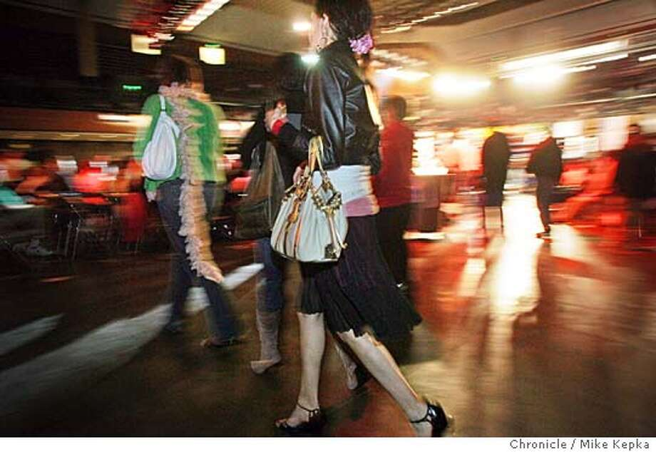 8:35 p.m. Clutching her Louis Vuitton bag, Nieves Ramirez rushes by to give luck to the fighters from 3rd Street Boxing Gym.  On Location at the 74th annual San Francisco Golden Gloves. 4/2/05 Mike Kepka / The Chronicle Photo: Mike Kepka