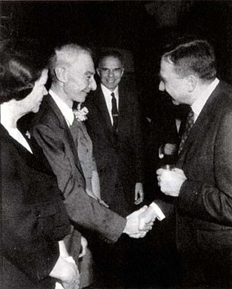"Robert Oppenheimer (left), after receiving the Fermi Prize from President Lyndon Johnson in 1963, is congratulated by former colleague Edward Teller (right). Teller had testified against Oppenheimer at a 1954 espionage hearing. Photo from ""American Prometheus''"