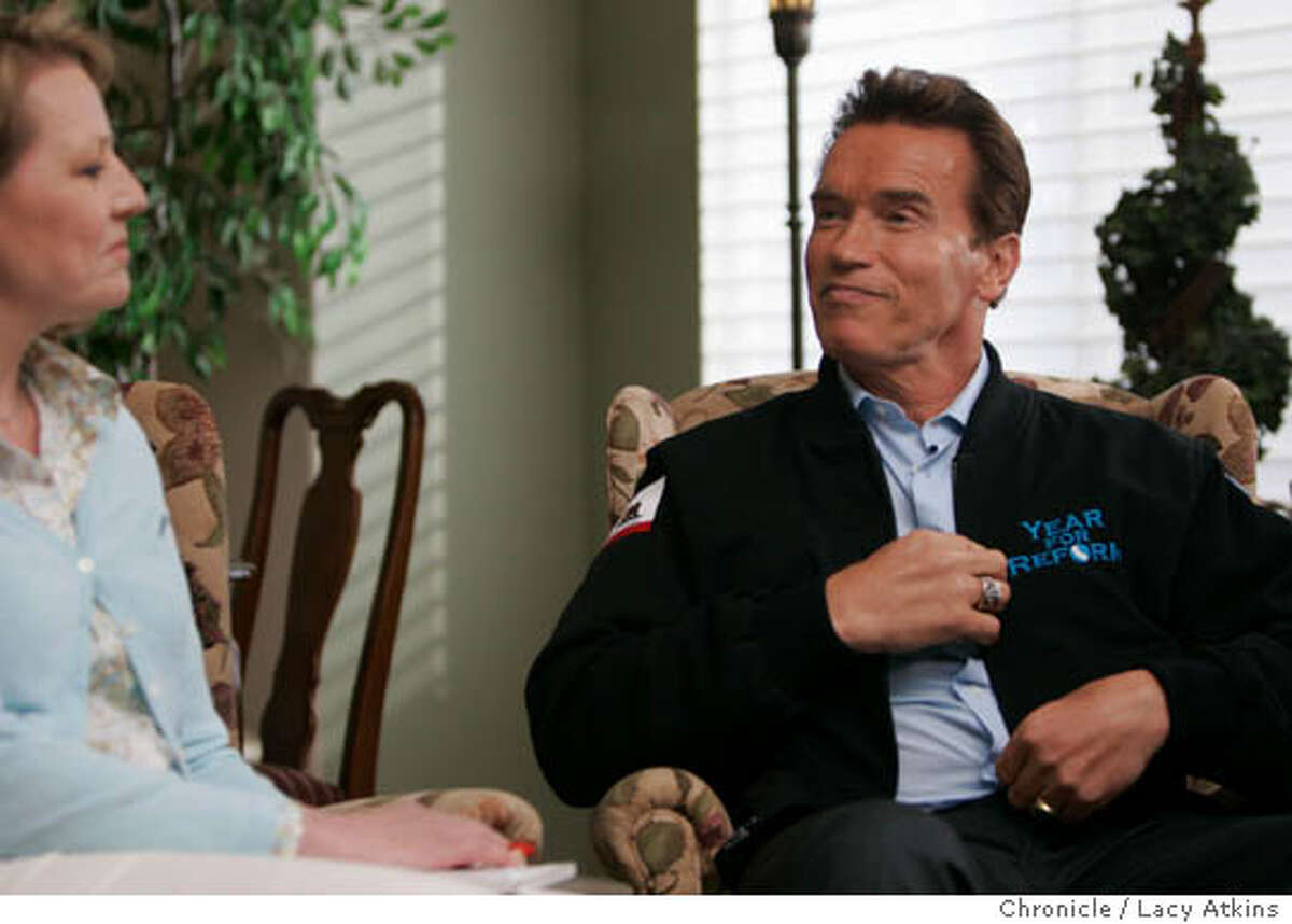 Governor Arnold Schwarzenegger talks about his jacket carrying the message of Year of Reform to Nancy Miller the owner of the home where the kitchen Cabinet meeting was held, April 7, 2005, in Santa Rosa. will give a press conference at 3 p.m. in Santa Rosa at the Hyatt Vineyard Creek, 170 Railroad Avenue. As pool photo and reporter, we will then be driven in motorcade over to the site of the