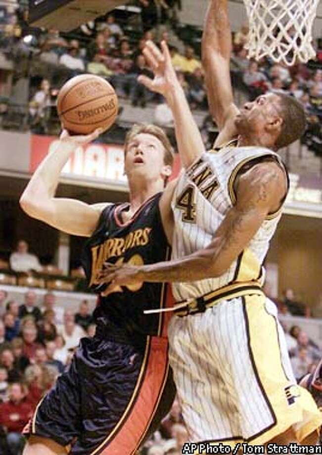 Golden State Warriors' Mike Dunleavy, left, is fouled as he puts up a shot against Indiana Pacers' Jonathan Bender, right, during the second quarter in Indianapolis, Saturday, Jan. 11, 2003. (AP Photo/Tom Strattman) Photo: TOM STRATTMAN