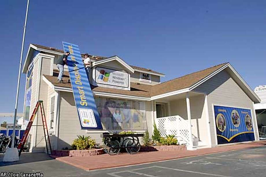 Frank Roskowski, left, and Gavin Thomson, subcontractors who work for Microsoft, lift a sign to the roof of a house built by Microsoft in the parking lot of the Las Vegas Convention Center, Tuesday, Jan. 7, 2003. The house will show off the Smart Display family of products as part of the Consumer Electronics Show which takes place in Las Vegas January 9-12.(AP Photo/Joe Cavaretta) Photo: JOE CAVARETTA