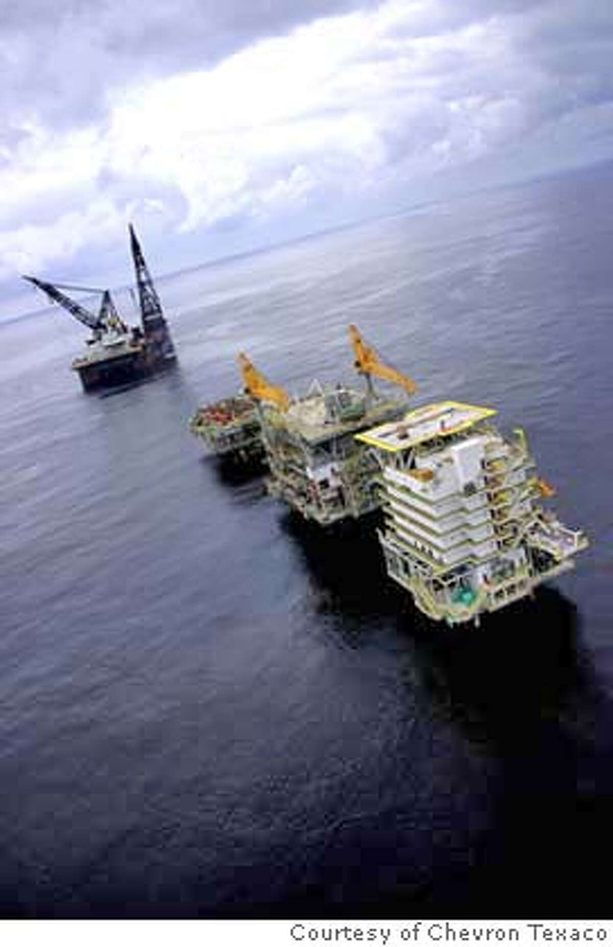 Photo of the Sanha Condensate Complex offshore Angola. Offshore Angola, The Sanha Condensate Complex consists of three bridge-connected platforms, one for drilling and production, one for processing and compression, and one for living quarters. In the distance is the semi-submersible Thialf, which lifted the Sanha topsides into place.