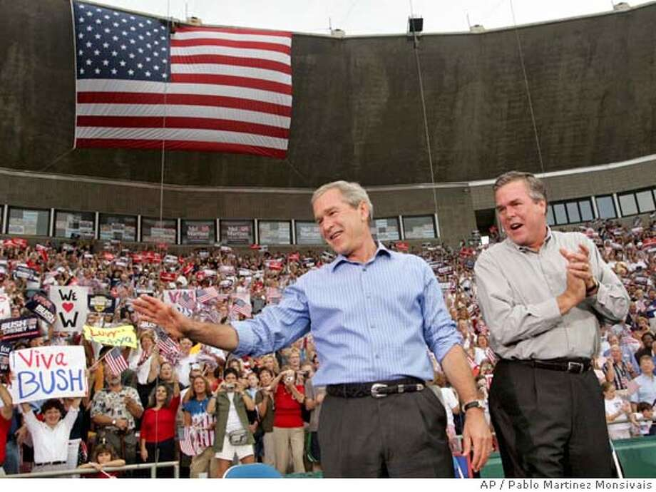 President Bush, left, waves to supporters as he is joined on stage with his brother Florida Gov. Jeb Bush, right, at Progress Energy Park-Al Lang Field during a campaign rally Tuesday, Oct. 19, 2004 in St. Petersburg, Fla. (AP Photo/Pablo Martinez Monsivais) Nation#MainNews#Chronicle#10/20/2004#ALL#5star##0422421397 Photo: PABLO MARTINEZ MONSIVAIS