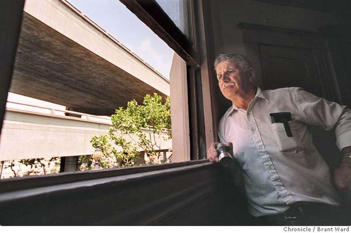 CENTRAL2/10JUL96/MN/BW-- (cq) looks out from the window of his apartment building on Market Street. He thinks they should tear down the whole Central Freeway...he's sick of it. By Brant Ward/chronicle