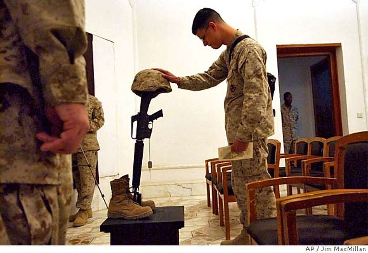 U.S. Marines pay their final respects at a memorial service for 1st Marine Division Combat Photographer Cpl. William Salazar, 26, of Las Vegas, Nev., at Camp Blue Diamond, on the outskirts of Ramadi, Iraq, Monday, Oct. 18, 2004. Salazar was killed in action in Anbar Province on October 15th. (AP Photo/Jim MacMillan)