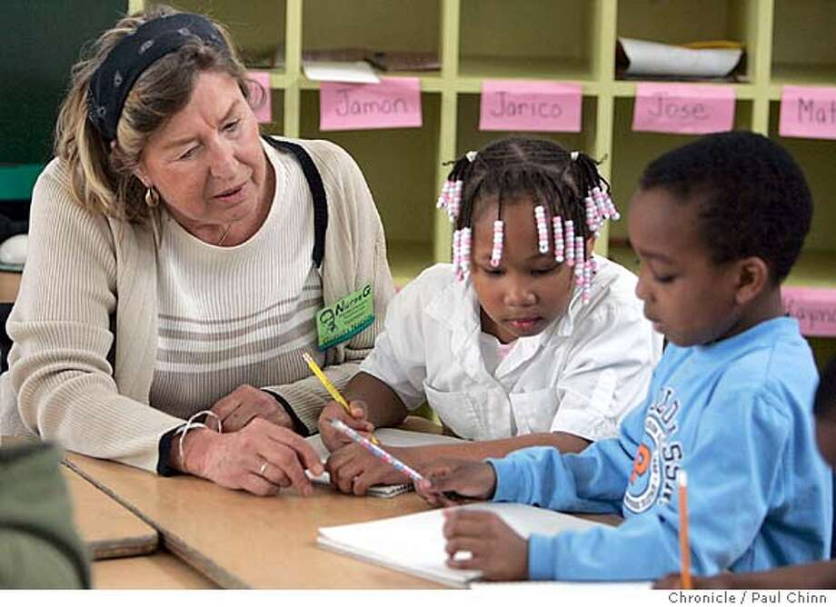 sfschools11_084_pc.jpg  Volunteer Gunilla Napier, the school's former nurse, helps first-graders Savannah Holloway and Andrew Williams write their names at Malcolm X Academy Elementary School on 4/7/05 in San Francisco, CA. It is one of several schools that SFUSD is considering for closure to help bridge a $10 million budget gap.  PAUL CHINN/The Chronicle MANDATORY CREDIT FOR PHOTOG AND S.F. CHRONICLE/ - MAGS OUT Photo: PAUL CHINN