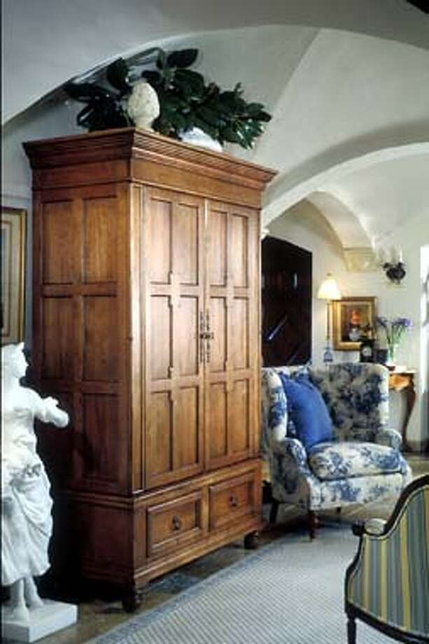 The hinged doors of this Harden armoire conceal an open storage area and several compartments with removable vertical dividers. A large piece like this serves as a focal point while adding storage.