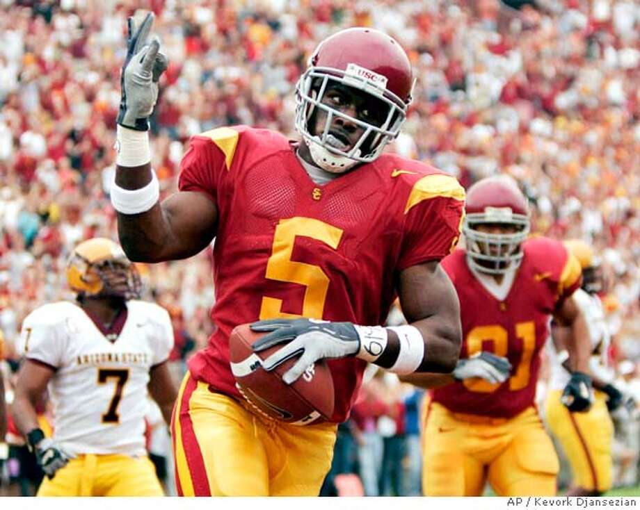 Southern Cal's Reggie Bush celebrates after scoring a touchdown against Arizona State during the first quarter of their PAC 10 football game Saturday, Oct. 16, 2004, at the Coliseum in Los Angeles. (AP Photo/Kevork Djansezian) Sports#Sports#Chronicle#10/19/2004#ALL#5star##0422416612 Photo: KEVORK DJANSEZIAN