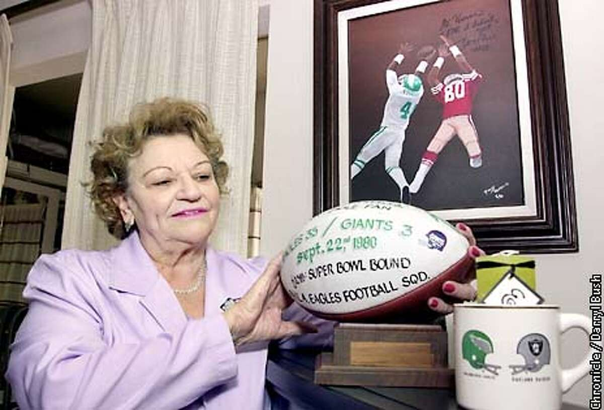 Martha Edwards mom of New York Jets coach, Herman Edwards, stands next to football memorabilia: 1) a football signed to