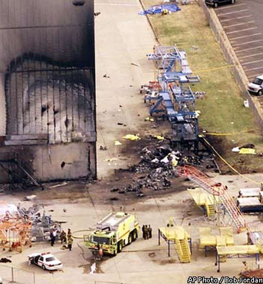 Emergency personnel are shown near the charred US Airways hangar after a commuter plane crashed into it at Charlotte/Douglas International Airport in Charlotte, N.C., Wednesday, Jan. 8, 2003. The crashed killed 21 people according to authorities. (AP Photo / Bob Jordan) Photo: BOB JORDAN