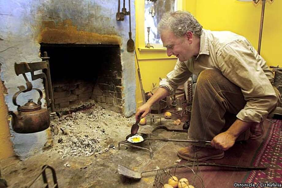 Days of Old: Using a long-handled, 1720s French egg spoon, William Rubel bakes an egg. Chronicle photo by Liz Hafalia