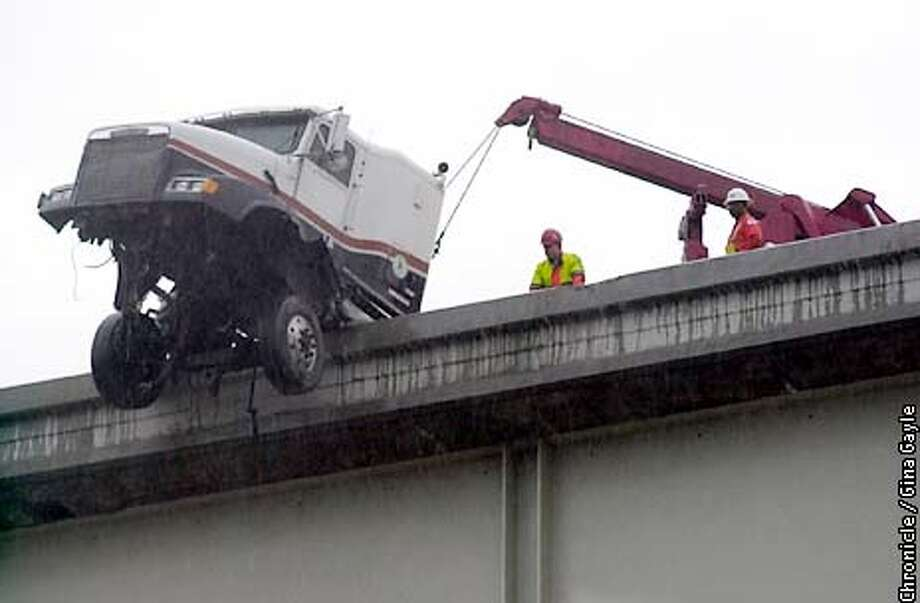 HANGINGa-C-09JAN03-MT-GG-A big rig truck hangs off of the I-880 and I-80 overpass. Highway workers look at the truck before it is removed from the overpass. The driver was removed safely. Photo by Gina Gayle/The SF Chronicle. Photo: GINA GAYLE