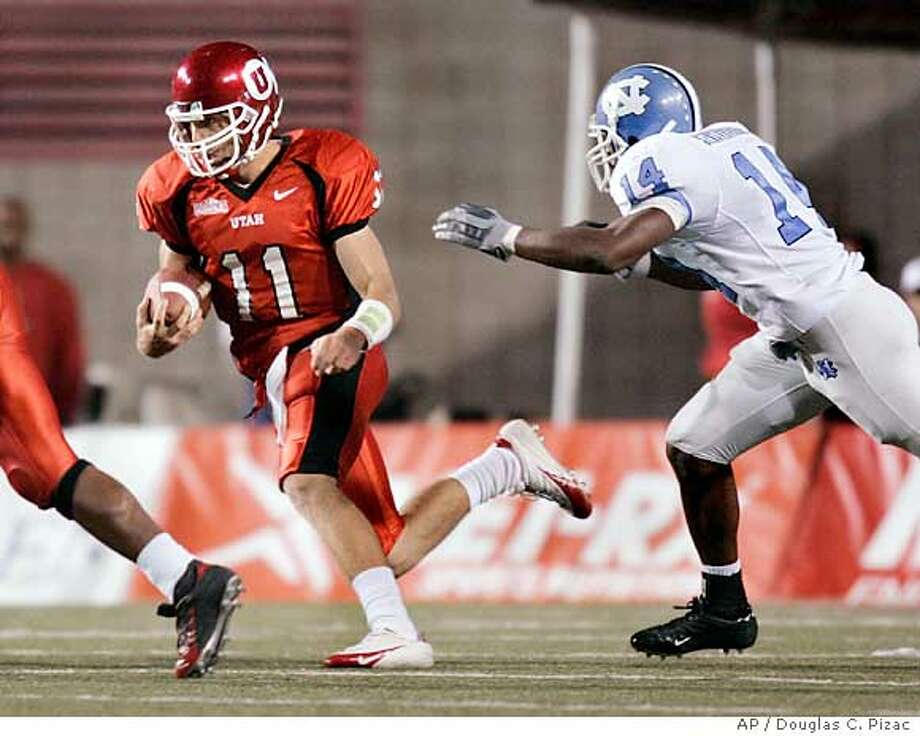 Utah quarterback Alex Smith (11) keeps the ball himself as he rushes for 19 yards before being tackled by North Carolina strong safety Gerald Sensabaugh (14) in the second quarter Saturday, Oct. 16, 2004, in Salt Lake City. (AP Photo/Douglas C. Pizac) Sports#Sports#Chronicle#10/18/2004#ALL#5star##0422417431 Photo: DOUGLAS C. PIZAC