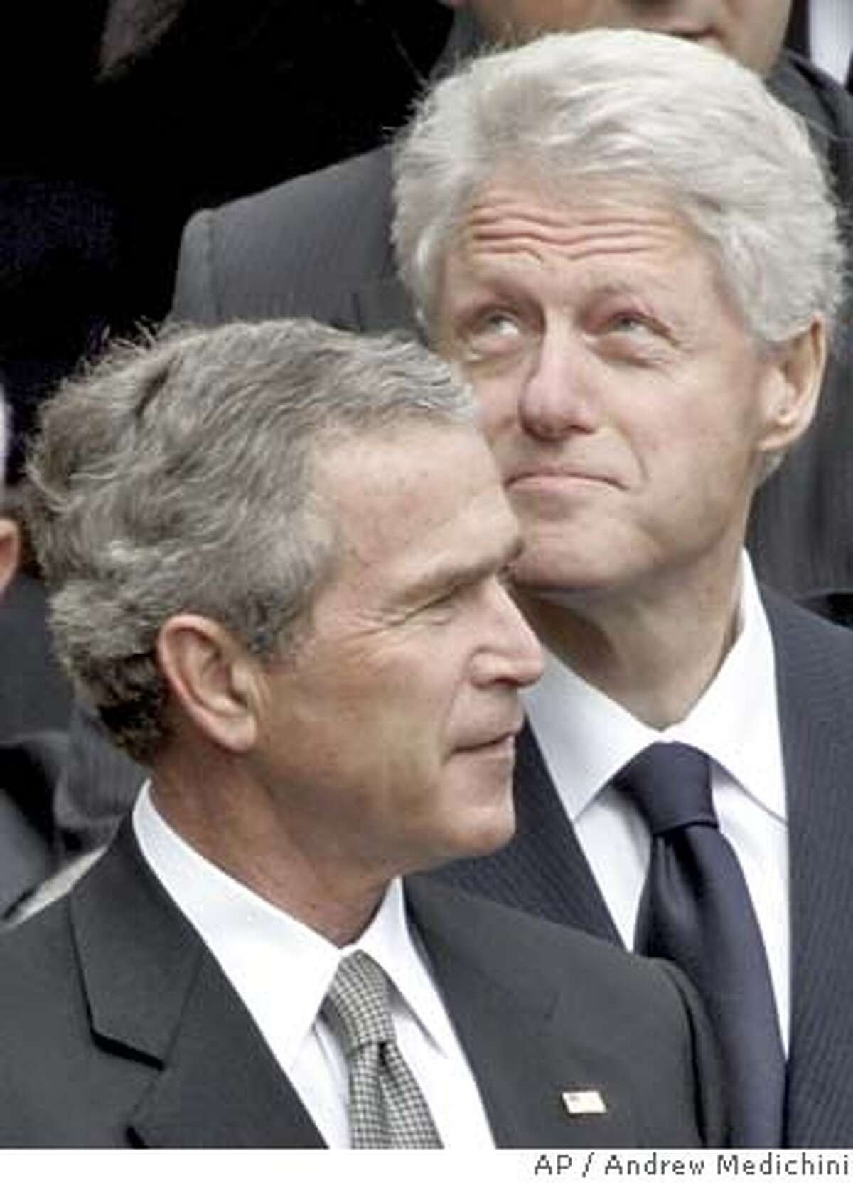 Former US President Bill Clinton looks up as President George Bush looks on after the funeral mass for Pope John Paul II in St. Peter's Square at the Vatican, Friday, April 8, 2005. (AP Photo/Andrew Medichini)