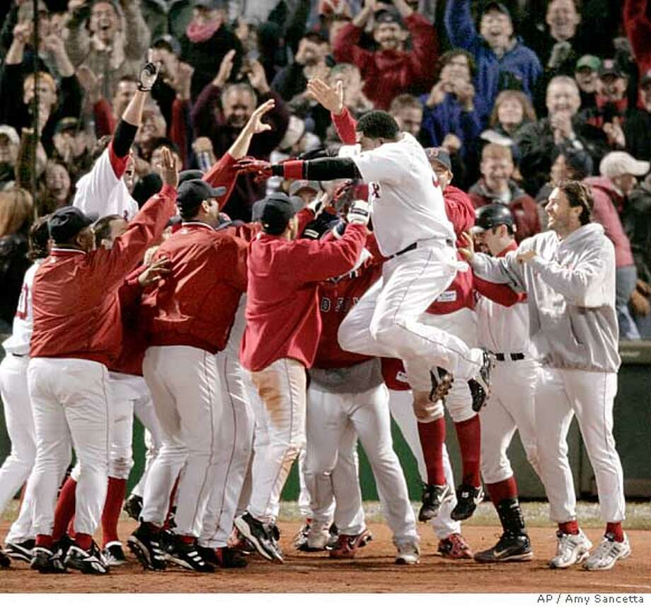 Boston Red Sox David Ortiz leaps into the waiting arms of his teammates as they celebrate his 12th inning game winning homer against the New York Yankees at Boston's Fenway Park in game four of the ALCS, Sunday Oct. 17, 2004. The Red Sox won, 6-4. (AP Photo/Amy Sancetta) Photo: AMY SANCETTA