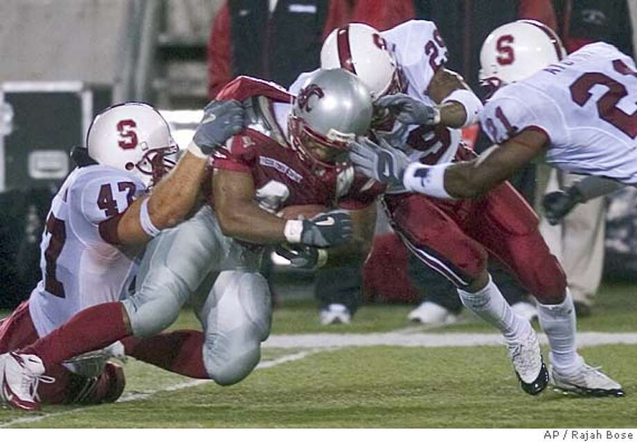 Washington State's Allen Thompson gets wrapped up by Stanford's Kevin Schimmelmann (47), Leigh Torrence (29) and Oshiomogho Atogwe (21) during the first half in Pullman, Wash., Saturday. Oct. 16, 2004. (AP Photo/Rajah Bose) Photo: RAJAH BOSE