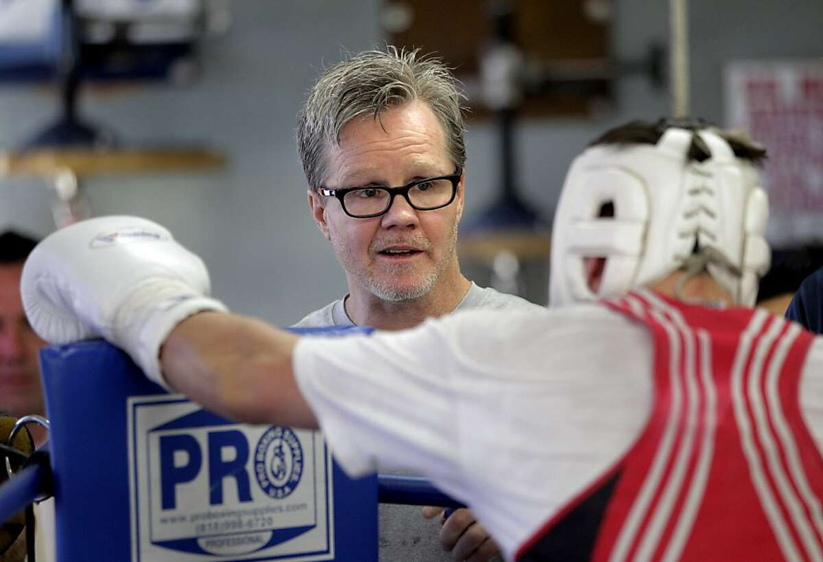 In this Friday, Jan. 13, 2012, photo, boxing trainer Freddie Roach works with a fighter at the Wild Card Boxing Club in Los Angeles. HBO's new documentary series about Roach will surprise many fans of the network's sports programming. Producers Peter Berg and Jim Lampley dispensed with narration or story lines, taking a verite approach as their cameras follow Manny Pacquiao's trainer through his eventful life. (AP Photo/Jae C. Hong)