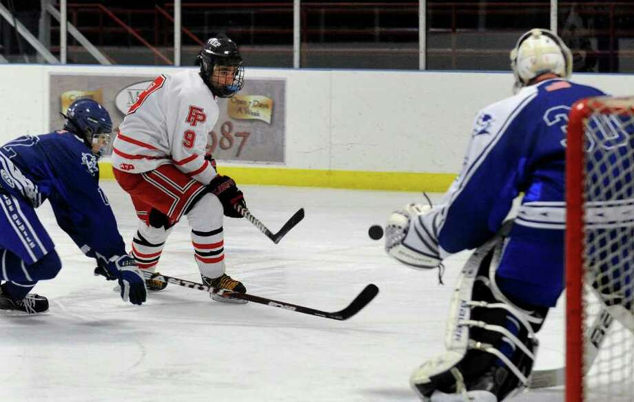 Fairfield Prep's #9 A.J. Unker attempts a goal shot as West Haven goalie Forest Schell, right, goes to block, during boys hockey action in Bridgeport, Conn. on Wednesday January 18, 2012. At left is West Haven's #12 Joe Ayala. Photo: Christian Abraham / Connecticut Post