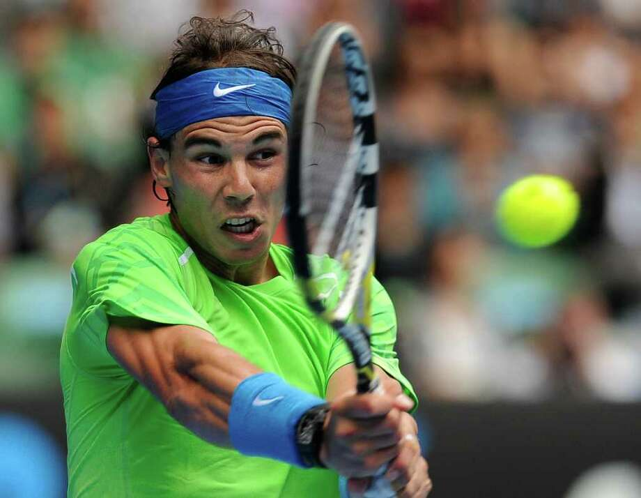 Spain's Rafael Nadal makes a backhand return to Slovakia's Lukas Lacko during their third round match at the Australian Open tennis championship, in Melbourne, Australia, Friday, Jan. 20, 2012. Photo: AP