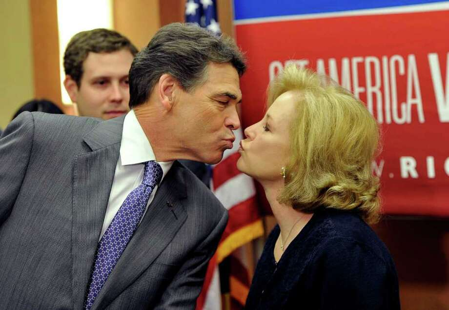 Texas Gov. Rick Perry kisses his wife, Anita, as he announces his campaign to be the Republican presidential candidate is over. Photo: MLADEN ANTONOV / AFP
