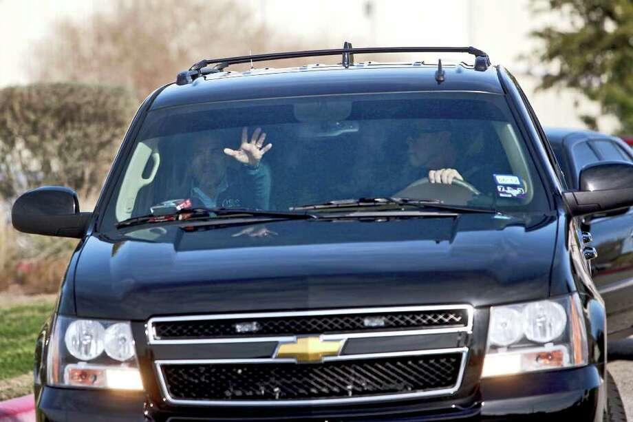 Gov. Rick Perry waves to the media as he leaves Atlantic Aviation on his arrival in Austin on Thursday. Photo: Lisa Krantz / @2012 SAN ANTONIO EXPRESS-NEWS
