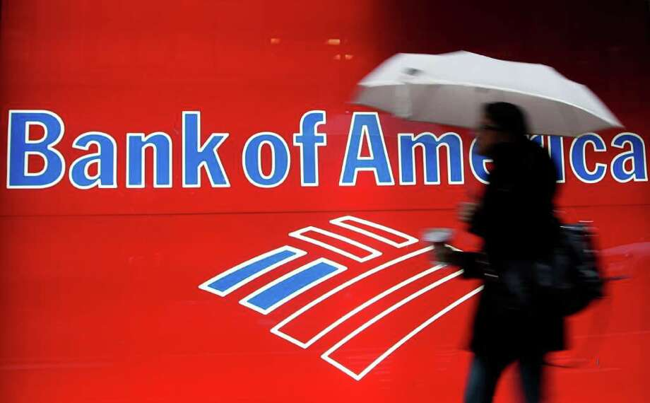In this Dec. 7, 2012 photo, a woman passes a Bank of America office branch, in New York. Bank of America said Jan. 19, 2012, it made $2 billion in the last three months of 2011 from selling its stake in a Chinese bank and selling debt. That offset losses and higher legal expenses in its mortgage business. (AP Photo/Mark Lennihan) Photo: Mark Lennihan / AP