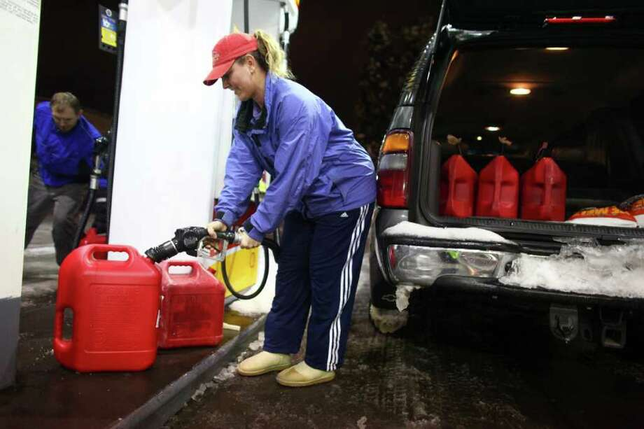 Jennifer Stone, who lives near Lake Tapps, stocks up on gas for her electric generator at a gas station in Auburn on Thursday, January 19, 2012. An ice storm wreaked havoc in the area, bringing down trees and power lines. Power was out in large parts of the region. Photo: JOSHUA TRUJILLO / SEATTLEPI.COM