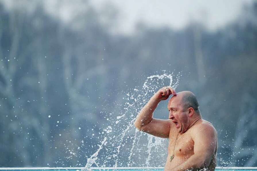A Russian Orthodox church faithful crosses himself as he marks Epiphany by plunging into the ice col