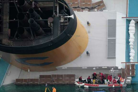 Rescuers work at the cruise ship Costa Concordia keeled over on its side in the tiny Tuscan island of Giglio, Italy, Thursday, Jan. 19, 2012. The $450 million Costa Concordia was carrying more than 4,200 passengers and crew when it slammed into well-charted rocks off the Tuscan island of Giglio. Eleven people have been confirmed dead and 21 others are still missing. (AP Photo/Gregorio Borgia)