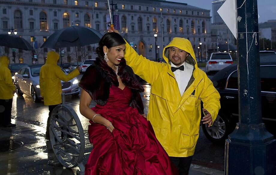 Shawna Gohel gets some help keeping her gown dry while arriving at the San Francisco Ballet Opening Night Gala at City Hall during a rainstorm in San Francisco, Calif., on Thursday, January 19, 2012. Photo: Laura Morton, Special To The Chronicle