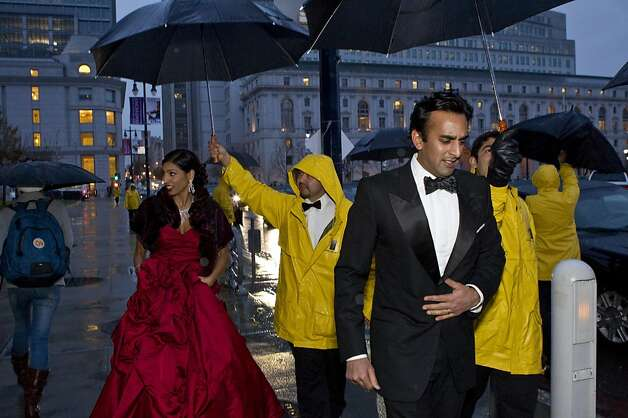 Shawna Gohel (left) and Anand Gohel get some help keeping themselves dry while arriving at the San Francisco Ballet Opening Night Gala at City Hall during a rainstorm in San Francisco, Calif., on Thursday, January 19, 2012. Photo: Laura Morton, Special To The Chronicle