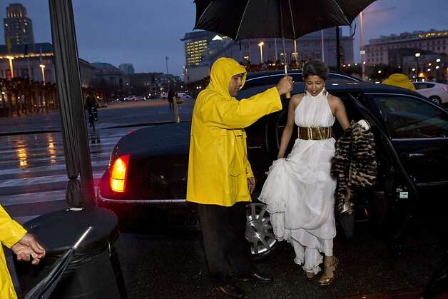 Deepa Pakianathan gets some help from a valet to keep her Alexander McQueen gown dry while arriving at the San Francisco Ballet Opening Night Gala at City Hall during a rainstorm in San Francisco, Calif., on Thursday, January 19, 2012. Photo: Laura Morton, Special To The Chronicle