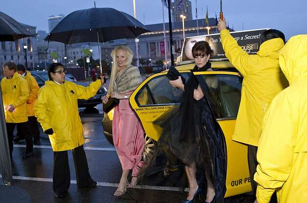 Penelope Murray (left) and Sarah Buckley get some help keeping their gowns dry while arriving at the San Francisco Ballet Opening Night Gala at City Hall during a rainstorm in San Francisco, Calif., on Thursday, January 19, 2012. Photo: Laura Morton, Special To The Chronicle