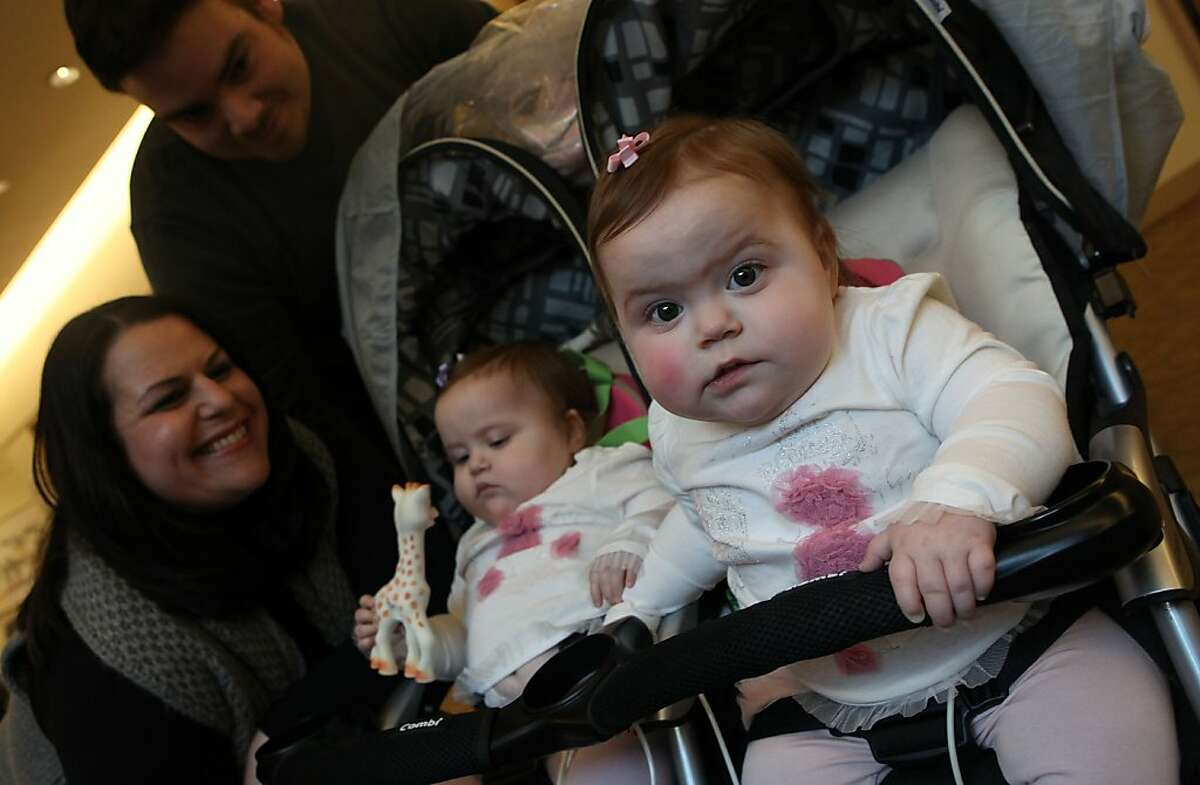Ricky Gonzalez (top left) andMegan Gonzalez (left) next to Charlotte Gonzalez (middle left) as Sophia Gonzalez (right), 16 month old twins from San Mateo, looks over in the lobby of Lucille Packard Children's hospital in Palo Alto, Calif., on Thursday, January 19, 2012. The twins were born a disorder called methylmalonic acidemia that inhibits the body?•s ability to break down protein and some fats. It was found through California?•s newborn screening program at Lucille Packard, which tests the most number of disease, and is more than anywhere else in the country.