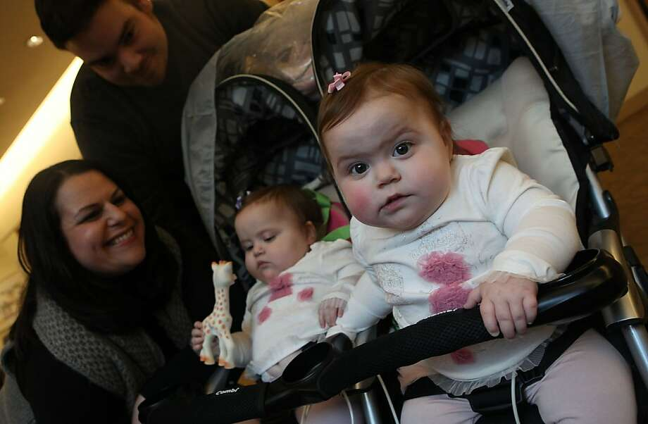 Ricky Gonzalez (top left) andMegan Gonzalez (left) next to Charlotte Gonzalez (middle left) as Sophia Gonzalez (right), 16 month old twins from San Mateo, looks over in the lobby of Lucille Packard Children's hospital in Palo Alto, Calif.,  on Thursday, January 19, 2012.   The twins were born a disorder called methylmalonic acidemia that inhibits the bodyÕs ability to break down protein and some fats.  It was found through CaliforniaÕs newborn screening program at Lucille Packard, which tests the most number of disease, and is more than anywhere else in the country. Photo: Liz Hafalia, The Chronicle