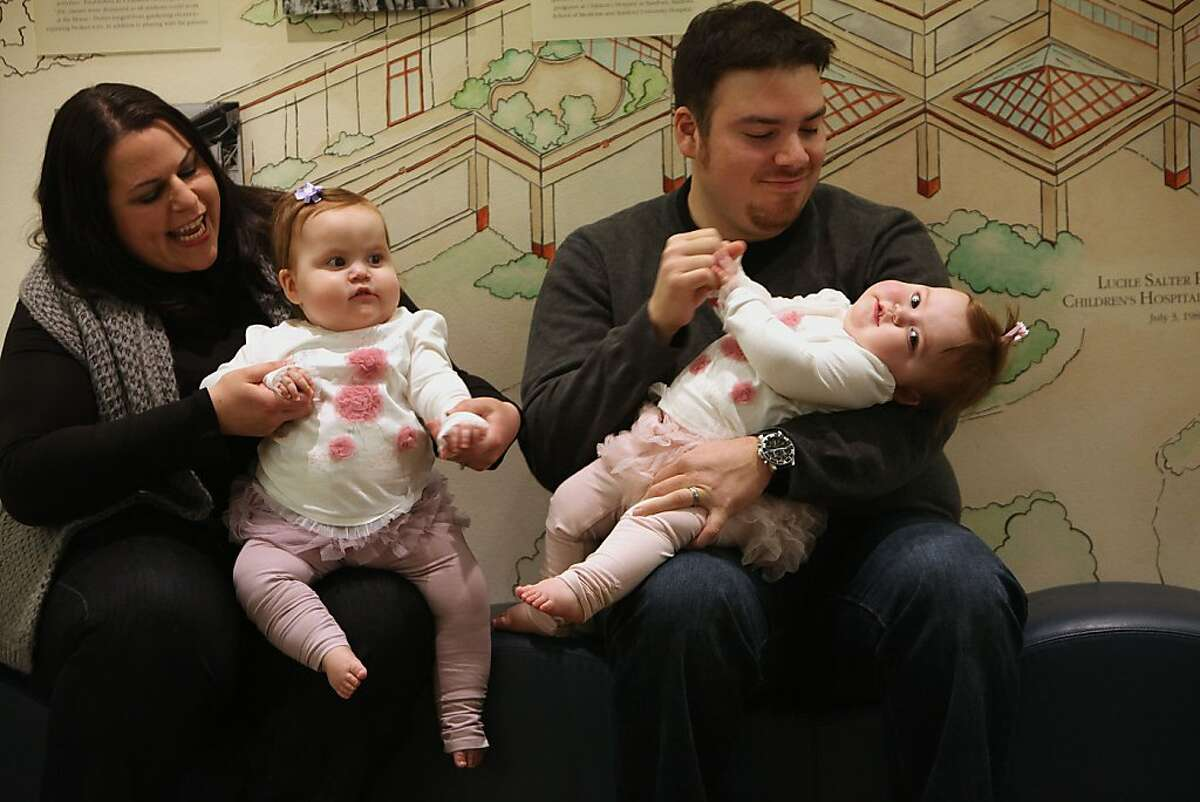Megan Gonzalez carrying Charlotte Gonzalez (left) and Ricky Gonzalez carrying Sophia Gonzalez (right), 16 month old twins from San Mateo, in the lobby of Lucille Packard Children's hospital in Palo Alto, Calif., on Thursday, January 19, 2012. California?•s newborn screening program at Lucille Packard tests the most number of disease, which is more than anywhere else in the country, and may be among the most sophisticated in the world.